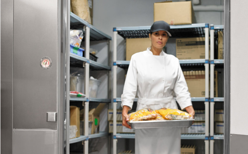 Foodservice worker walking out of Kolpak freezer/cooler