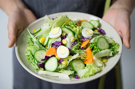Man holding plate with salad with eggs, cucumber toppings